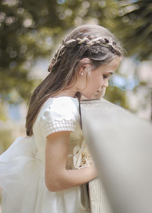 una nina vestido para su comunión pone su barbilla en una barandilla