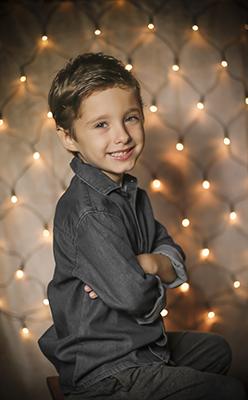 un niños vestido de gris sonrie en frente de luces de navidad