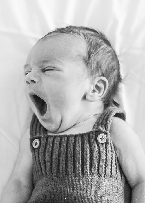 un bebe newborn bosteza hacia la izquierda