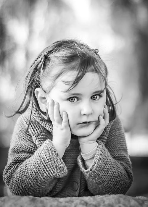 una nina sujeta su cabeza con sus manos mientras que mira al camera