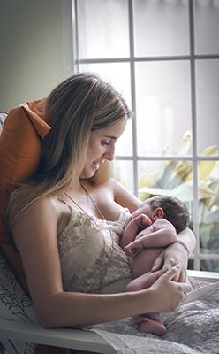 un mama dando pecho al bebe sentada en frente de la ventana