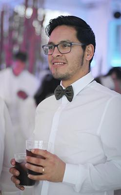 Un invitado al una boda sonriendo a la derecha con dos basos en su manos