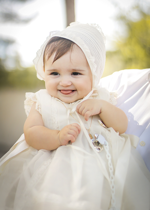 una bebe sonrie en el sol despúes de su bautizo