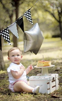 una bebe sentada en el césped con su tarta de cumpleaños
