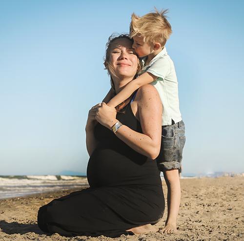 Una embarazada de rodillas en la playa abrazando su hijo rubio y sonriendo