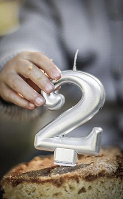 Un niño coje el numero 2 de su tarta en la fiesta de cumpleaños