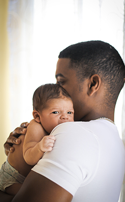 un bebe newborn mirando del hombro de su padre