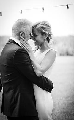 los novios sonrien mientras que tocen sus cabezas en sus boda