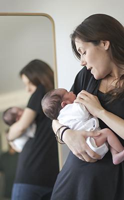 Una mama joven y guapa con su bebe newborn en sus brazos