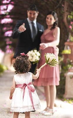 una niña ofrece una rama de flores a una pareja en una boda en la iglesia