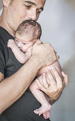 un papa besa la cabeza de su bebe mientras que le abraza