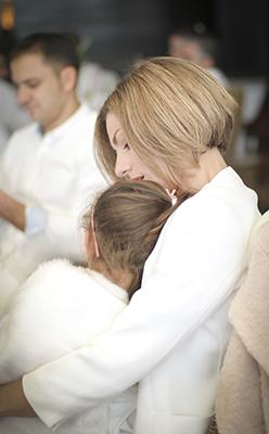 una niña y una mama abrazen en una boda con todos vestidos de blanco