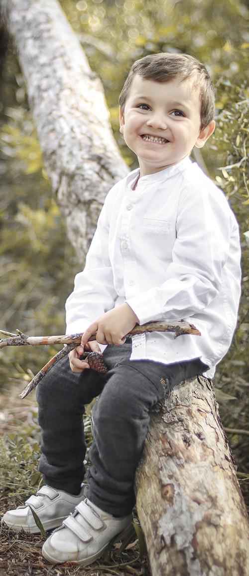 Un niño sentado en una rama de un arbol con ramas en sus manos
