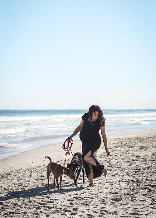 Una mama embarazada en la playa de la malvarosa con sus dos perros