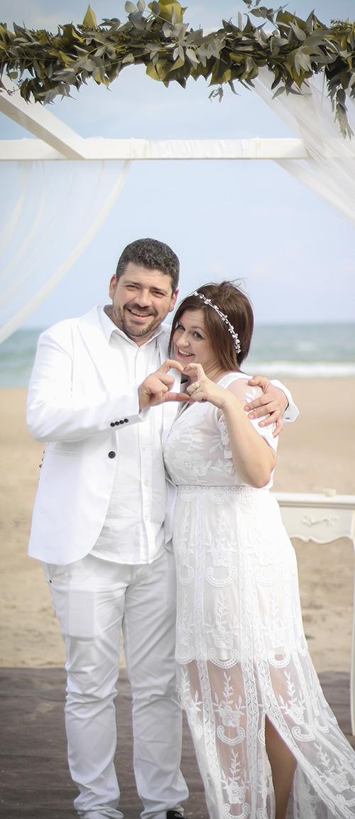 una pareja sonrie al camera mientras que forman una corazon con sus manos despues de sus boda
