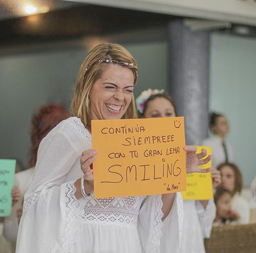 La novia sonrie mientras que sujeta una carta con un mensaje de amor de una amiga