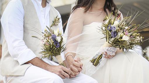 los novios en una boda sentados cogiendose los manos tienen ramas de flores