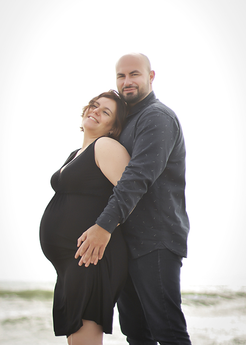 una pareja joven con la mujer embarazada abrazandose en la playa del el saler, valencia