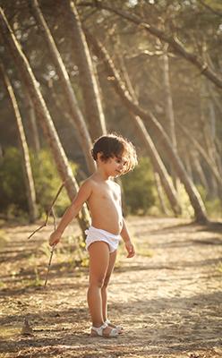 un niño pequeño en el bosque vemos arboles al fondo