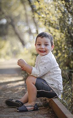 un ninos sentado en el campo sonrie al camera
