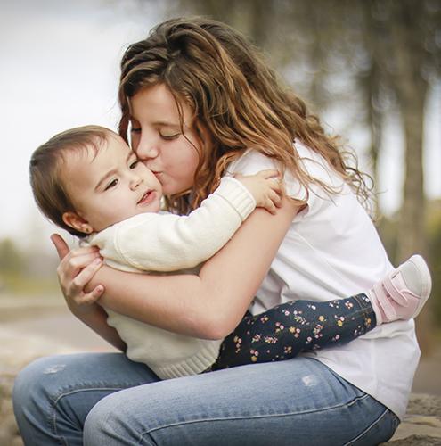 una hermana major de unos 10 años besa su hermana pequeña