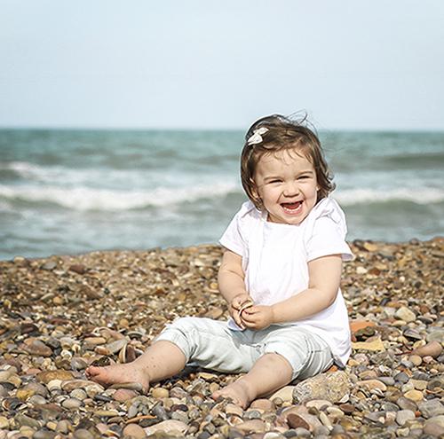 Una niña pequeña sentada en una playa de piedras con el mar detras de ella