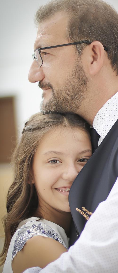 Una niña sonrie al camera mientras que abraza su papa en una boda