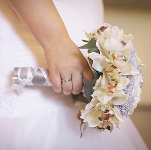 una rama de flores en el mano de la novia en la dia de su boda