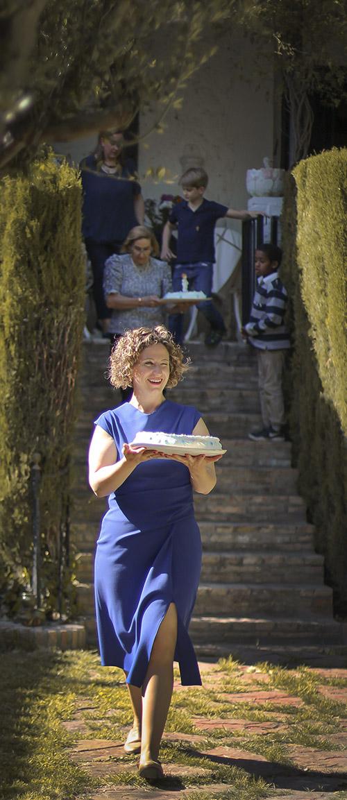 una mujer con una tarta en sus manos vemos mas personas detras de ella bajando al jardin con comida