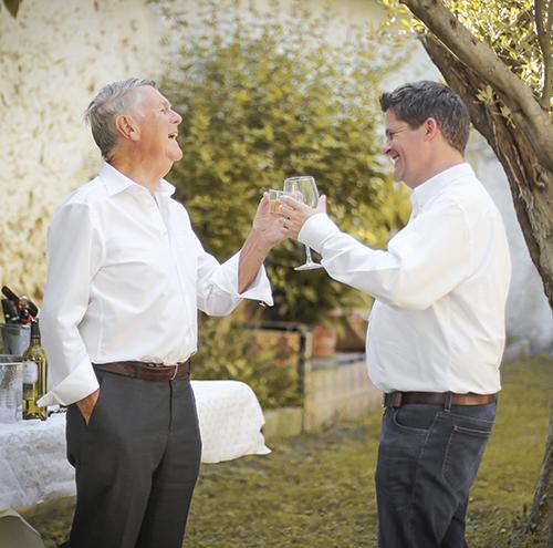 dos hombre en camisas bridan en un jardín en una fiesta de comunión