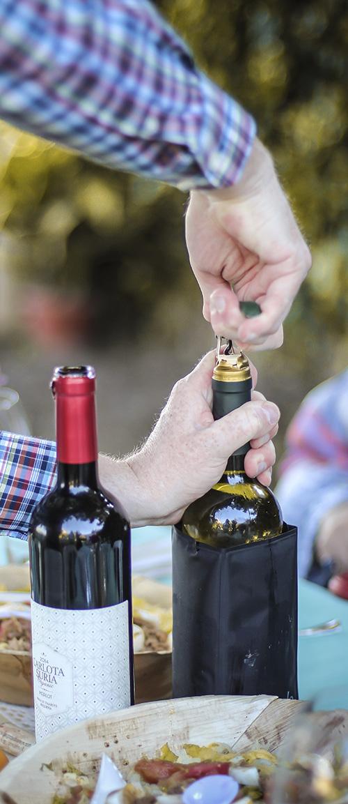 un mano saca el corcho de una botella de vino en una fiesta de comunion