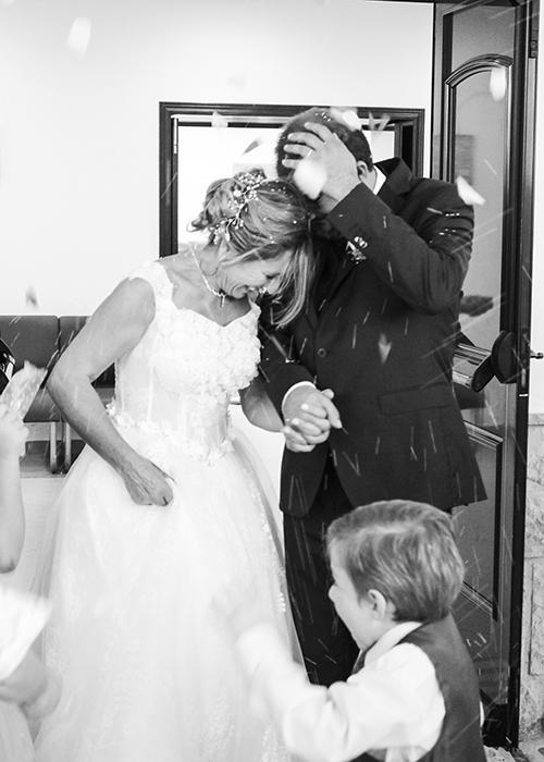 una pareja recien casados sonriendo mientras que se aparten del arroz que les tiren