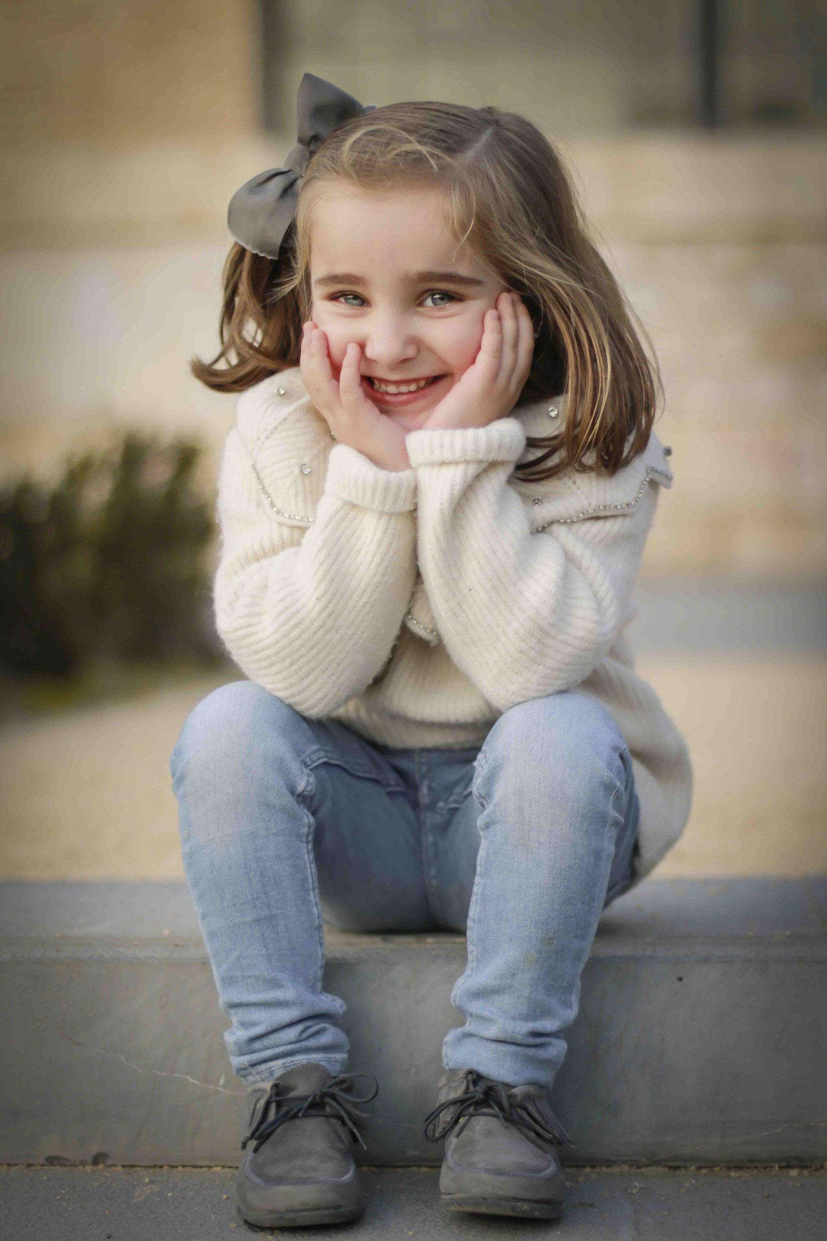 una niña que lleva gorro, guantes y bufanda  sentada en el suelo sonriendo
